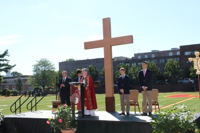Fr. Garrett Long S.M. '62 reads the homily at the Triumph of the Cross prayer service.