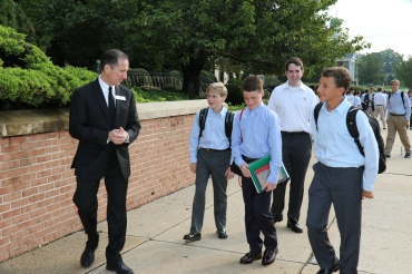 Bro. Thomas Cleary '81 greets new freshman to Chaminade High School along with Senior Leader Colin Maloney '15 (second from right).
