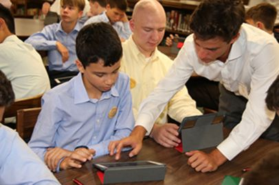 A Senior Leader helps a new freshman with his iPad during 3-C Week.