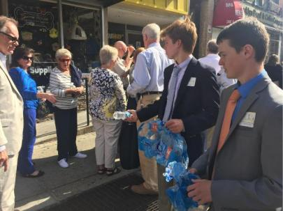 (l.-r.) Clark Newby '17 and Sean Maleady '17 hand out water bottles to thirsty congregants on the long line to enter MSG.