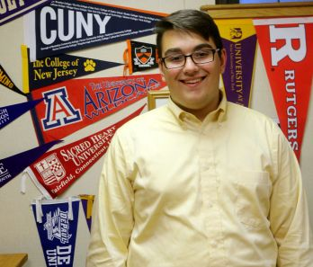 Anthony Hubner '17 stands in front of the various pennants in the College Placement Office.