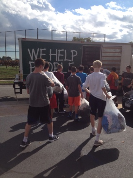 Sophomore GSO helps load the clothing donations onto St. Vincent de Paul's iconic truck.