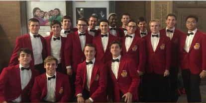 Members of the Vocal Chamber Ensemble, dressed in their signature red jackets and black bow ties, assemble for a group shot in front of Carnegie Hall.