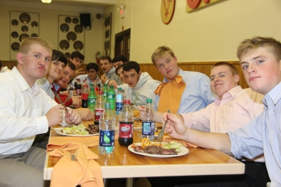 A group of seniors makes comical faces for the camera while enjoying sugary drinks, steak, and fries.