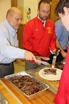 Mr. Thomas Giovannetti and Mr. Beirne '00 serve steak to hungry seniors.