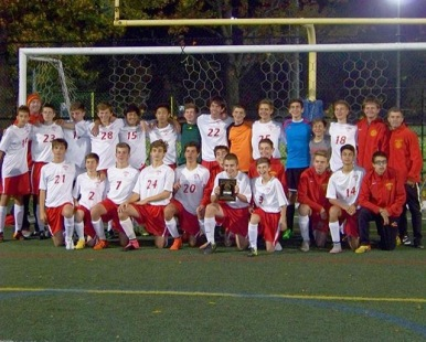 The entire Freshman soccer team roster stands proudly displaying their CHSAA championship plaque.