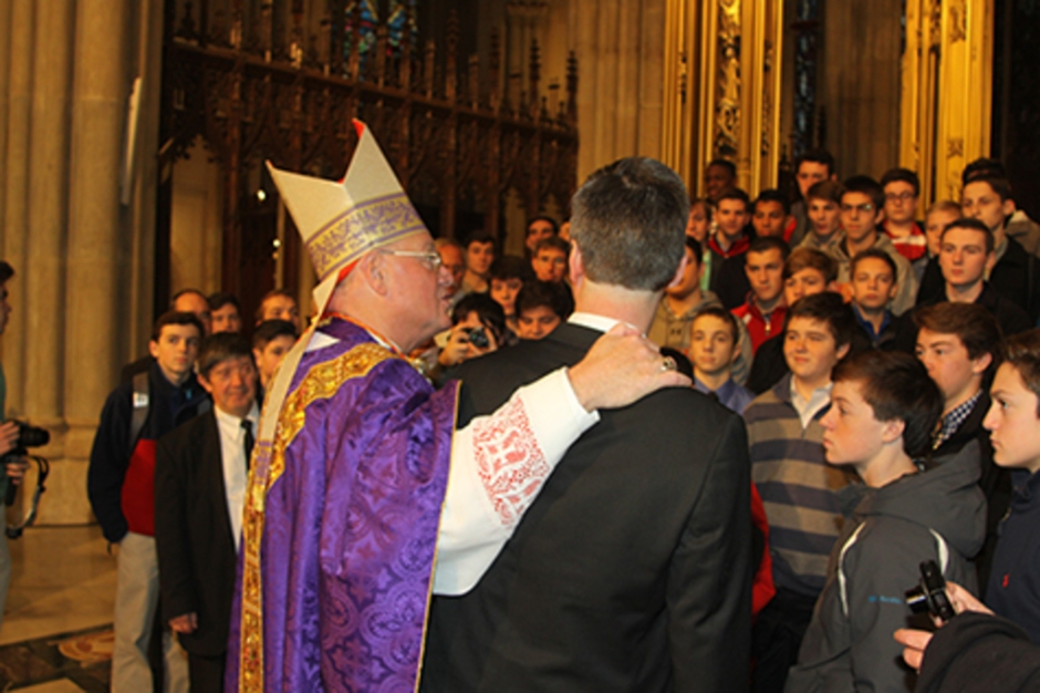 Cardinal Dolan, with his arm around Bro. Peter S.M. '86, speaks to the Chaminade pilgrims before a group photo.