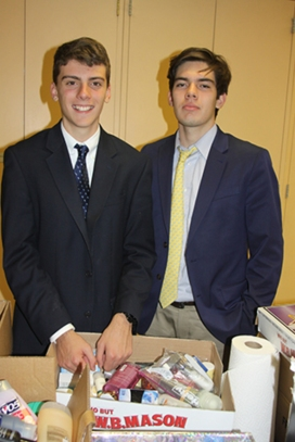 (l.-r.) Seniors Sean Galligan and Christian Hurley sort the supplies for delivery to the Queen of Peace Residence.