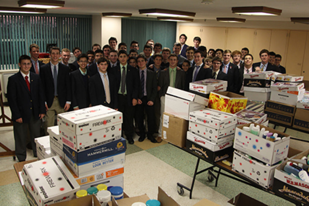 Students who delivered the supplies to Queen of Peace proudly pose in front of the boxes of donations.