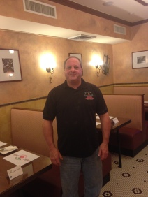Bob Bernam, owner of Plum Tomatoes pizzeria, stands near some of the restaurant's seating.