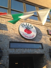 The sign above the door proudly displays the name the Mineola pizzeria, Plum Tomatoes.