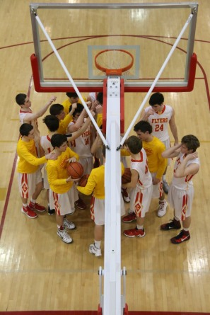 The Chaminade varsity basketball team gets ready to break after huddling under the net.