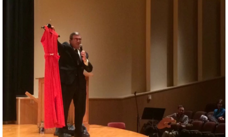 Brother Stephen Balletta S.M. '74 holds up a red dress and explains the story of Teresa from Homeboy Industries.