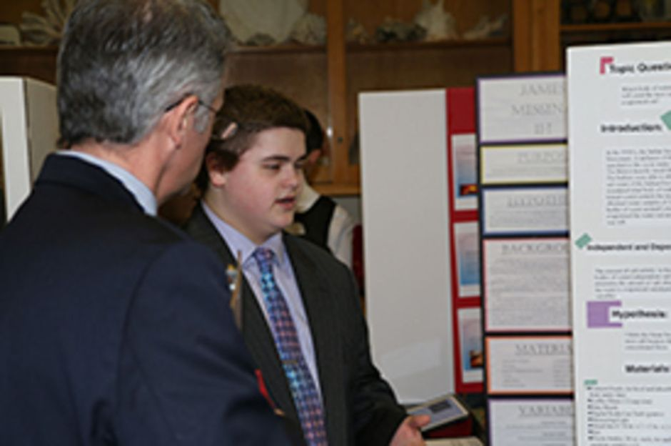 Joseph Moses '19, winner of the Earth Science division of the science fair, explains the specifics of his project to Mr. Dennis Flood '89.