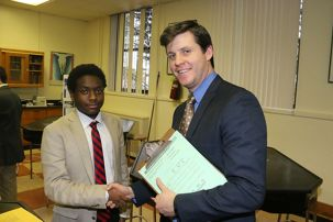 "Kenneth Bradley '18 shakes hands with Mr. Andrew Corcoran '01 after the judging of the project, ""Effects of Iron on the Reproduction of Chlorella Vulgaris""."