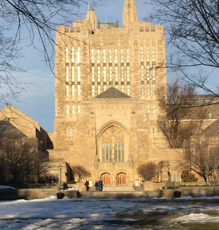 The fields in front of one of Yale's collegiate gothic buildings is partially covered in melting snow.