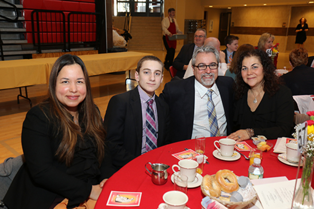 Chaminade Spanish teacher Mrs. Rita Santiago-Espinal joins the Carrano family for breakfast.