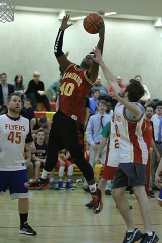 Tyler Toussaint '16 jumps up to shoot a layup while Mr. Sebastian Agosti '09 attempts to block his path to the net.