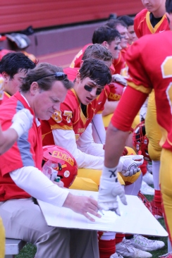 An experienced and well-respected coach, Stephen Boyd draws up a plan during one of this year's varsity football games.