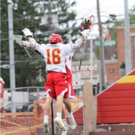 Two Chaminade offensive JV lacrosse players chest-bump in mid-air in a fit of celebration.