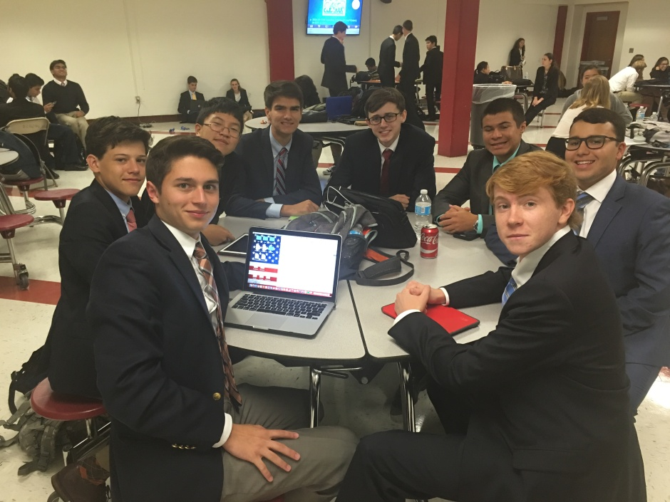 Chaminade's Public Forum debaters gather between rounds to update each other on their performances.