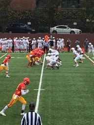The offense blocks the Fordham Prep defense as a running back rushes the ball.