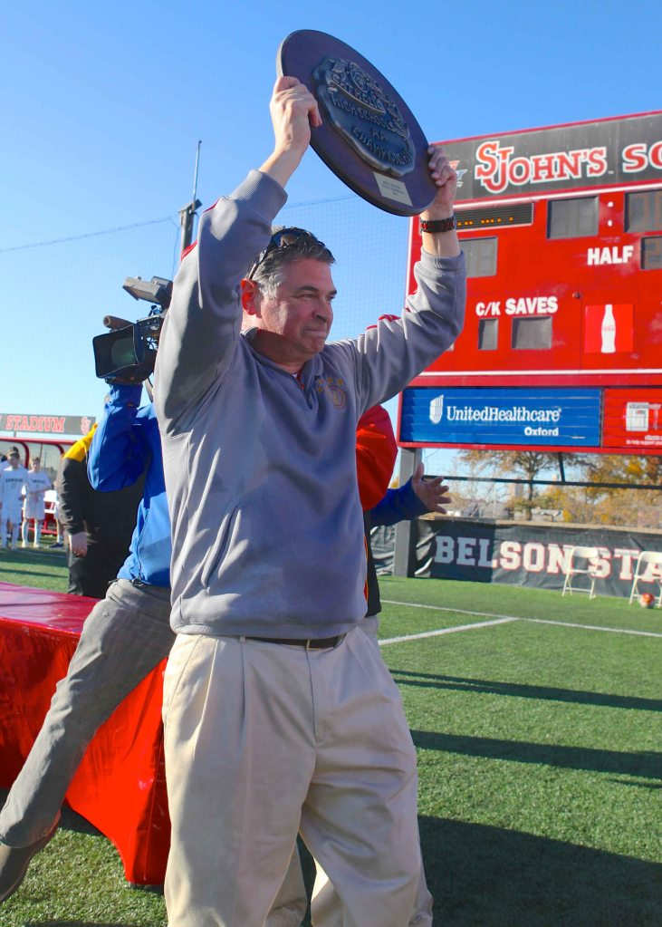 Head Coach Mr. Michael Gallagher hoists the NYSCHSAA trophy overhead after claiming the Flyers' second consecutive state championship. Photo Credit: Geoff Walter '01.