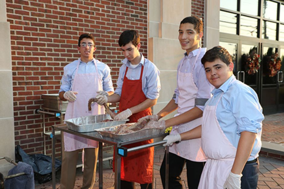 Members of the Culinary Club barbecue a steak dinner for the hungry seniors.