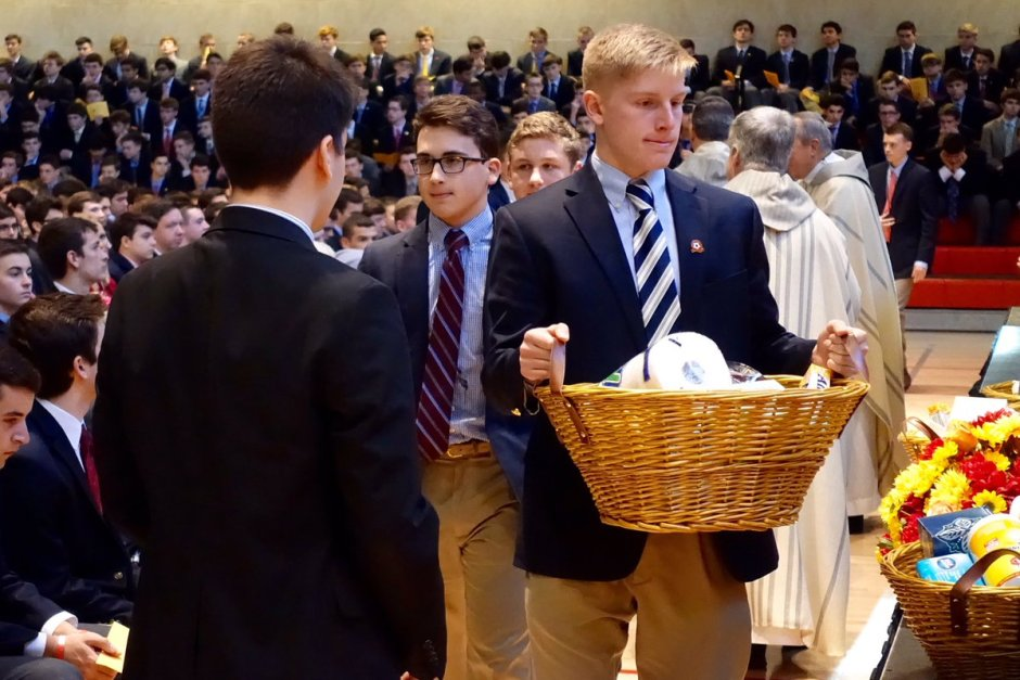 Nicholas Milano '17 places a basket filled with toiletries on the altar prior to Communion.