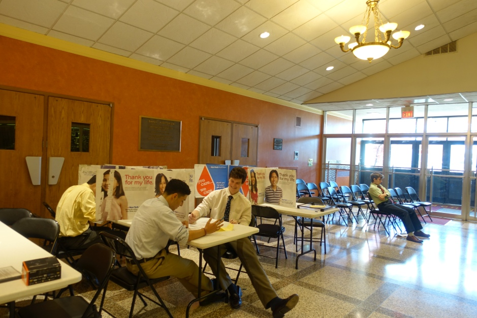 Seniors fill out the proper information as they wait patiently in the lobby before they donate blood.