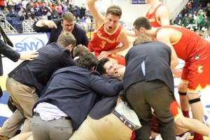 The victorious Flyers form a dog pile upon completing their 85-65 win over Holy Trinity.